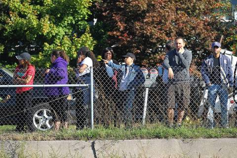 Spectators watch emergency teams deal with two CTA Blue Line trains that collided at the Harlem stop in Forest Park.