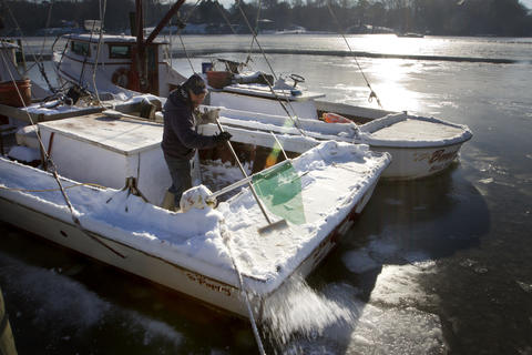 Leon Nicosia sweeps ice from the stern of the Samantha K on Thursday. Ice kept oystermen at their berths Thursday. The last day of the oyster harvest season for the James River is Jan. 31.