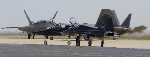 Heat waves from jet engines envelop T-38's and F-22's as they gather for last flight checks before rolling out for a training sortie Wednesday from Langley Air Force Base.