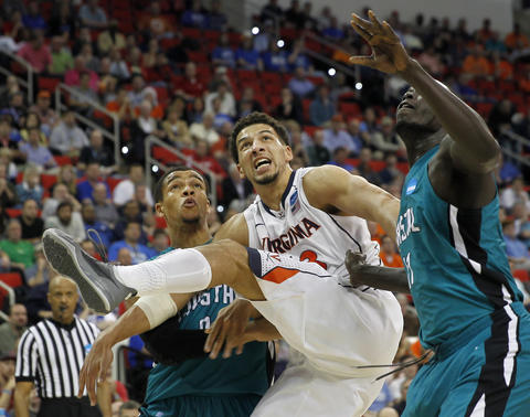 Virginia's Anthony Gill, center, battles for position during the second half of Friday's second round NCAA tournament game against Coastal Carolina.
