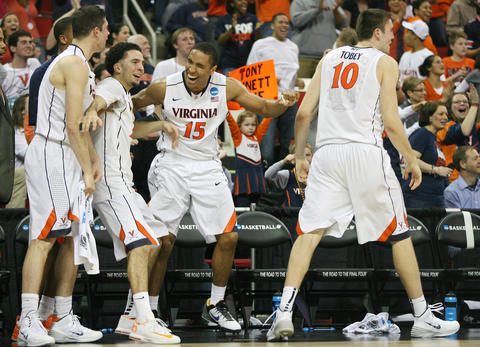 Malcolm Brogdon and the Virginia bench react to an Evan Nolte dunk in the closing minutes of Sunday's third round NCAA tournament game in Raleigh.