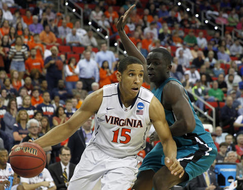 Virginia's Malcolm Brogdon drives past Coastal Carolina's Badou Diagne during the second half of Friday's second round NCAA tournament game in Raleigh.