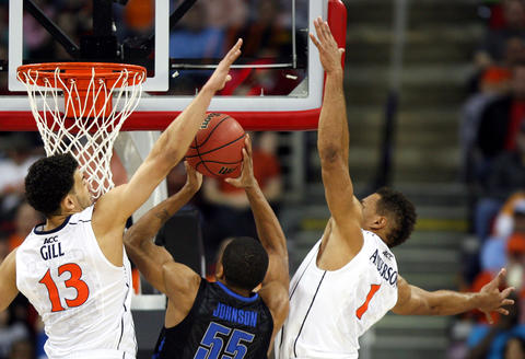 Virginia's Anthony Gill and Justin Anderson block a shot by Memphis' Geron Johnson during the first half of Sunday's third round NCAA tournament game in Raleigh.