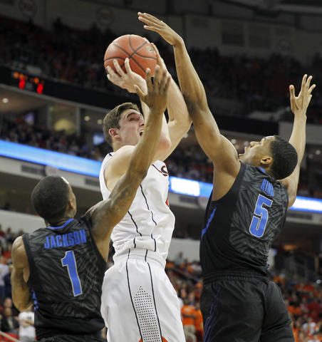 Virginia's Joe Harris shoots over Joe Jackson and Nick King of Memphis during the first half of Sunday's third round NCAA tournament game in Raleigh.
