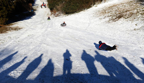 Sledders take to a steep hill in Yorktown Wednesday after Tuesday night's snowstorm dropped a couple of inches on the area.