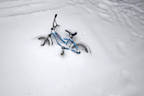 A bicycle is covered in snow Wednesday morning in Hilton Village.
