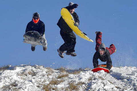 From left, Spencer Satchell, 16, Carter Ashley, 14, and Nick Long, 15, jump into the air to gain speed while sledding down a hill at Riverview Farm Park in Newport News Wednesday morning.