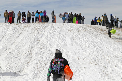 Sledders fill the top of the hill at Riverview Farm Park Wednesday afternoon.