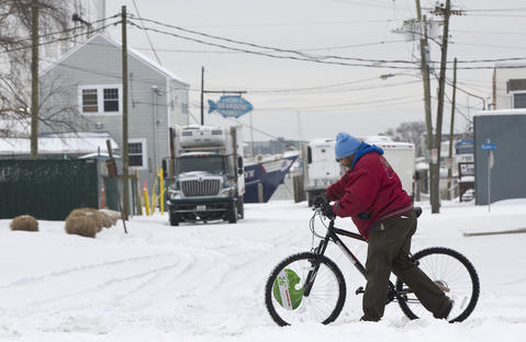Patrick Bland walks home from working at Walmart along a snow-covered Settlers Landing Road early Wednesday morning.