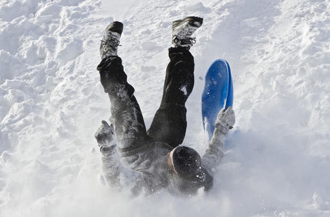 Zach Shaffer, 17, wipes out while sledding down a hill at Fort Monroe on Wednesday afternoon.