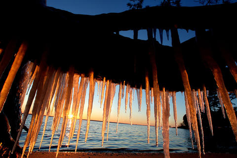 Icicles hanging from a tree root along the James Rivers are backlit by the setting sun Friday evening. Temperatures should warm slightly over the weekend.