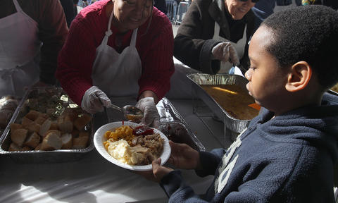 Taryke Thompson gets a Thanksgiving meal at the annual Feeding 5000 Community Celebration at the Newport News Farmers Market. No Mags, No Sales, No Internet, No TV