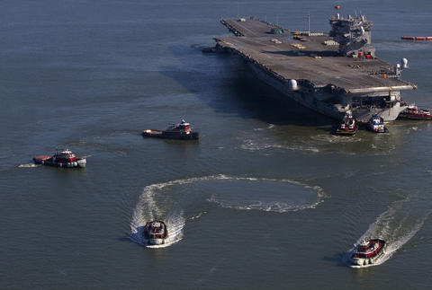 Tugboats tow the USS Enterprise into the Newport News Shipyard on Thursday.