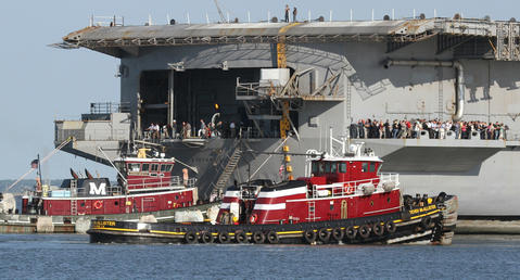 USS Enterprise enters a berth at Newport News Shipbuilding early Thursday for the last time as the ship enters the final stages of its service to the United States.