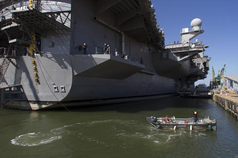 A small craft moves around the stern of the USS Enterprise to bring lines to Pier 2, the ship's berth for the next three years where it will undergo inacvtivation.