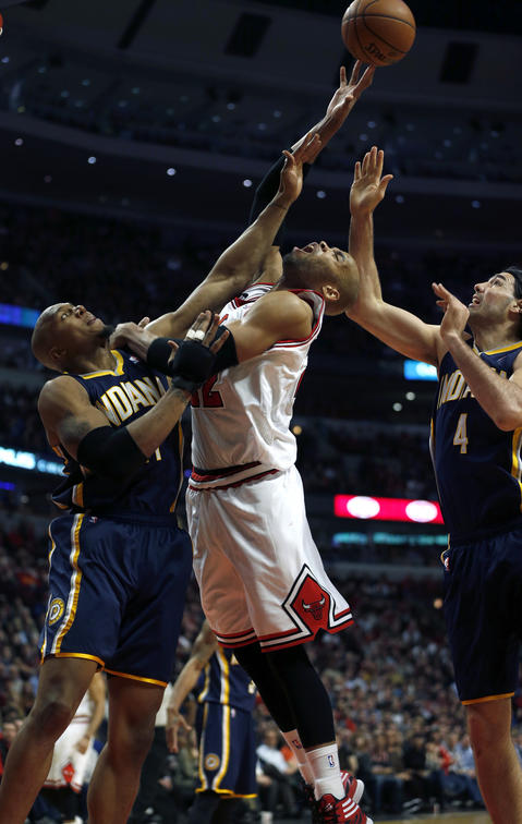 Taj Gibson is fouled by the Pacers' Luis Scola (right) as David West defends in the 4th quarter.