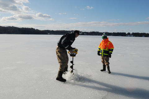 While Shalyn Zappulla watches, at right, Ian Croci digs a hole through the ice.