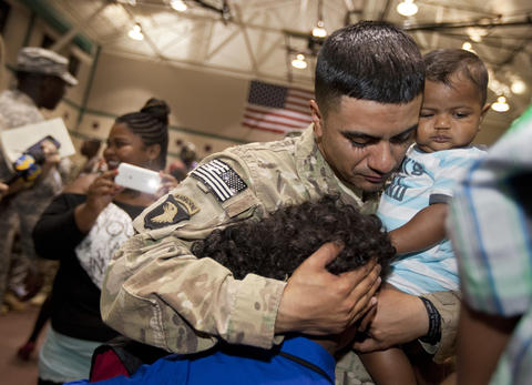 Sgt. Luis Flores greets his sons, eight-year-old Jalen Flores and nine-month-old Javeon Flores after arriving home with the 359th Transportation Company at Fort Eustis on Monday evening.