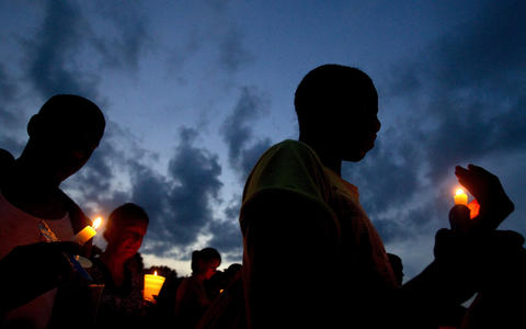 Imontae Parker (right) stands with others on the Phoebus High School soccer field during a vigil for Caitlin Kremp, 18, who died in a hiking accident in Colorado. Kremp was the salutatorian of Phoebus High School's Class of 2011 and served as the captain of the girls soccer and field hockey teams.