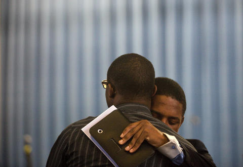 Benjamin Mesadieu and Craig Washington embrace following a memorial service for Hampton University freshman David Esan, who died following a pool party on campus on March 20.