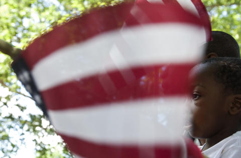 Jovenie Tankeu and his two-year-old nephew Yahya Tchatchoua, of Cameroon, listen to remarks during a Naturalization Ceremony in Colonial Williamsburg on Friday, June 14.