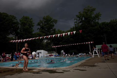 Storm clouds darken the sky during a Hidenwood Tarpons inter-squad swim meet at Hidenwood Pool in Newport News on Thursday, June 13.