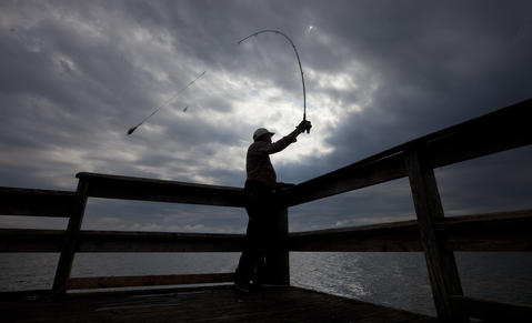 Arthur Lockhart casts a line from the Hilton Pier under cloudy skies on Tuesday afternoon.