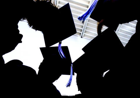 Peninsula Catholic High School grads put their heads together before the ceremony started. Joe Fudge Photo Gallery.