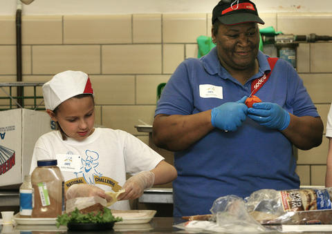Making Apple Jack Turkey Sandwich, Julia Shrieves, third grade Waller Mill Elementary, cooks alongside helper Zennie Parrott.