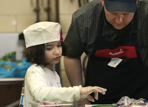 Taleen Timani, third grader from Coventry Elementary, gets help from Tim Miller in assembling Guma Vegggie.