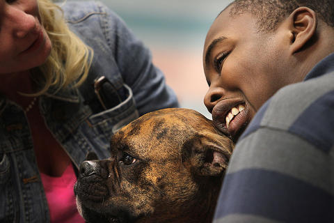 Stacey Kopp, left, brings her boxer therapy dog, Louie, to a special needs class at Jamestown High School, much to the delight of Tavian Gabriel.