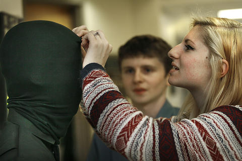 York County School of the Arts will be performing George Orwell's 1984. Besides rehearsal of the play, there is a lot of behind the scenes activity performed by the students.   Costume designer Emily Steinmiller adjusts the mask of Ickye Delgado-Cruz, who plays a guard; watching is Logan Taaffe.