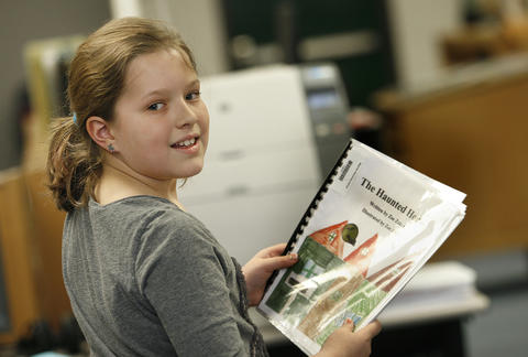 "Magruder Elementary has a program that publishes students' work into books, then places them in the library for other students to check out.  Zoe  Zaken, walks through the library with her book, ""The Haunted House""."