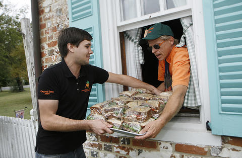 The Carrot Tree restaurant in Yorktown, which rents from the National Park Service, opened for lunch despite its forced closure due to the federal government shutdown. John Schuszler, left, delivers sandwiches from an open Carrot Tree through the front window to Glenn Helseth. The lunch will be a limited menu of sandwiches, ham biscuits, brunswick stew and carrot cake.