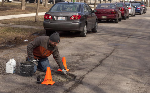 Jim fills his chosen pothole at 5223 W. Argyle Street with mortar, which is three equal parts of concrete, white lime and river sand.