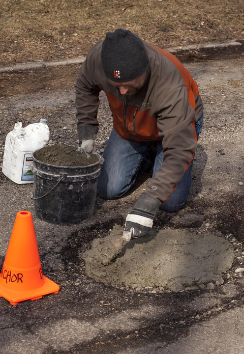 Jim fills his chosen pothole at 5223 W. Argyle St with mortar, which is three equal parts of concrete, white lime and river sand.