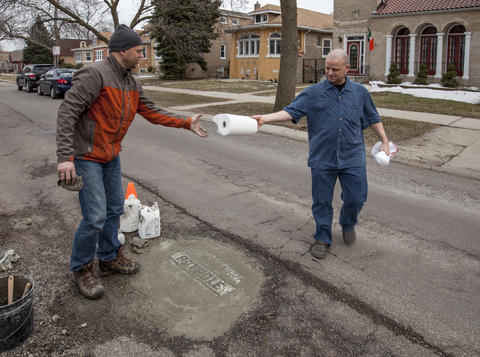Bill Spain, who lives in the neighborhood, donates a roll of paper towels to help Jim clean up the excess water and cement.