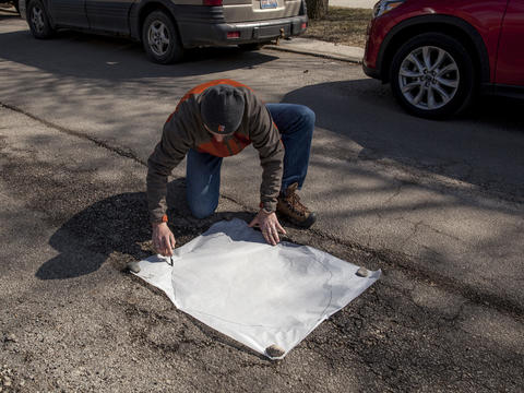 Jim traces the pothole's dimensions to compare with the size of his art work.