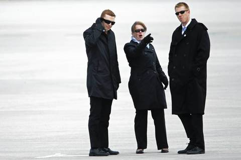 Secret Service agents talk before the arrival of Air Force One at O'Hare International Airport, in Chicago. President Barack Obama was in town to attend fundraisers for the Democratic National Committee.