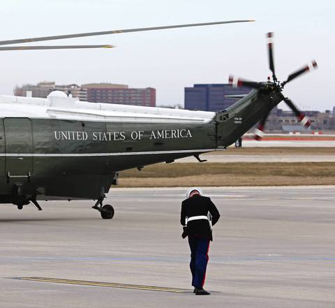 A U.S Marine lowers his head to shield himself from the wind generated by the presidential helicopters at O'Hare International Airport, in Chicago. President Barack Obama was in town to attend fundraisers for the Democratic National Committee.
