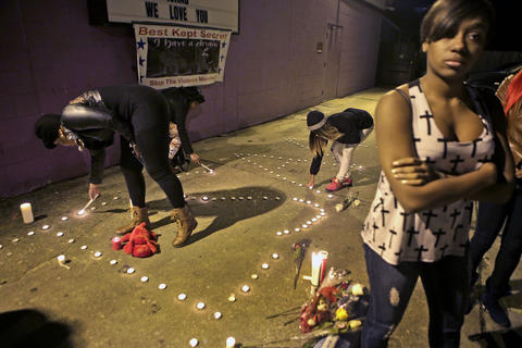 Friends and family lights candles during a vigil for Isaac Oshin outside Majik City Gentlemen's Club and Sports Bar Friday evening. Dozens of people gathered outside the club to remember Isaac Oshin who was shot to death inside the club at 5825 Jefferson Avenue Wednesday evening.
