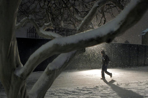 Christopher Newport University junior Zach Martin walks through campus Wednesday evening as snow flies through the air and begins to accumulate on a trees.