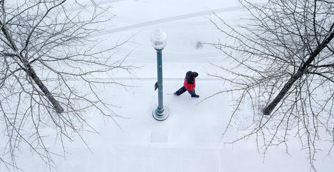 As snow begins to fall Wednesday at City Center a lone figure heads home down Lakefront Commons.
