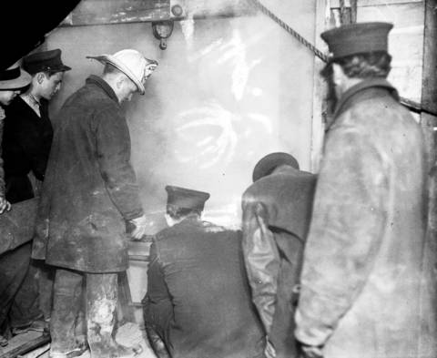 """Workers and firemen surround the smoke-filled entrance to the intercepting sewer tunnel at 22nd and Laflin Streets on April 13, 1931. According to the Tribune, """"It was down this shaft that fireman after fireman was lowered during the morning hours."""""""