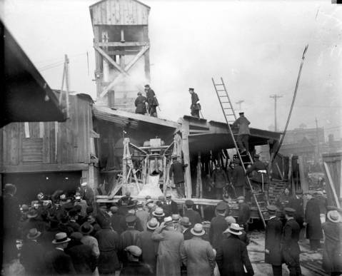Fireman hack away with axes at the roof of the superstructure above the elevator shaft in hopes of ventilating the tunnel. Albert Martino, a cement worker, testified later that he heard an explosion in the tunnel around 6:30 on Monday evening. He said he found a light flame in the tunnel and vainly tried to extinguish it and then notified other laborers and officials. Many thought the fire started when candle wax dripped on sawdust in the tunnel.