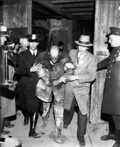 A fireman is assisted from the scene after a trip down the elevator shaft into the sanitary district tunnel on April 13, 1931. Many firefighters went into the smoke-filled tunnel without masks or oxygen tanks.