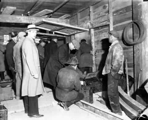 """Workers and firemen surround the smoke-filled entrance to the intercepting sewer tunnel on April 13, 1931. According to the Tribune, """"It was down this shaft that fireman after fireman was lowered during the morning hours."""""""