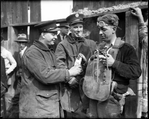 """Fireman Irving Strom, 28, of Squad 8, right, takes a cigarette from fellow firefighters during the tunnel disaster. Strom volunteered to use a newer type gas mask delivered from the Oak Park fire department. According to Tribune reports, Strom made seventeen trips into the tunnel and brought up six bodies and one person alive. """"It was hot down there,"""" Strom said later, """"and so thick with smoke and fog that lights were of no avail. All one could do was to grope slowly through the tunnel, often bumping into obstructions."""""""