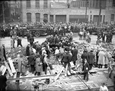 """According to the Tribune, on April 14, 1931, """"Groups of men dug feverishly beneath the pavement of 22nd Street to reach the concrete [sanitary district] tunnel, the top of which is seventeen feet below the surface."""" They hoped to dig holes in the tunnel and rescue the firefighters and laborers who had been trapped 35 feet below the surface overnight. Bystanders watched the progress from across 22nd Street."""
