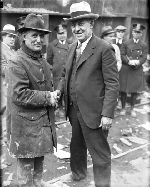 Division Marshal Patrick J. Egan, left, shakes hands with Peter Pirsch, the manufacturer of the smoke ejector, which was used to rescue 16 men from the unfinished sanitary district tunnel fire on April 14, 1931. Pirsch drove the smoke ejector from Kenosha, Wisc. when he heard of the disaster. The ejector was able to blow out the deadly smoke and fumes, allowing firefighters to rescue the 16 workers and firefighters that were trapped overnight in an air chamber in the tunnel. Fire Chief Charles W. Ringer of the Minneapolis fire department invented the machine.